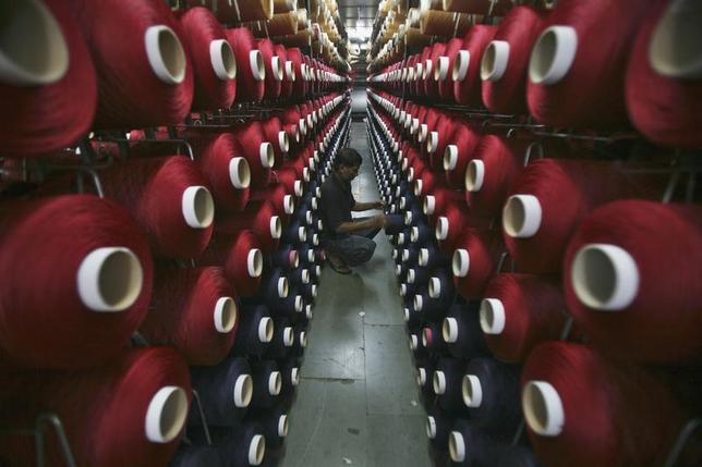 An employee works at the production line of a carpet manufacturing factory in Jammu September 12, 2013. REUTERS/Mukesh Gupta/Files