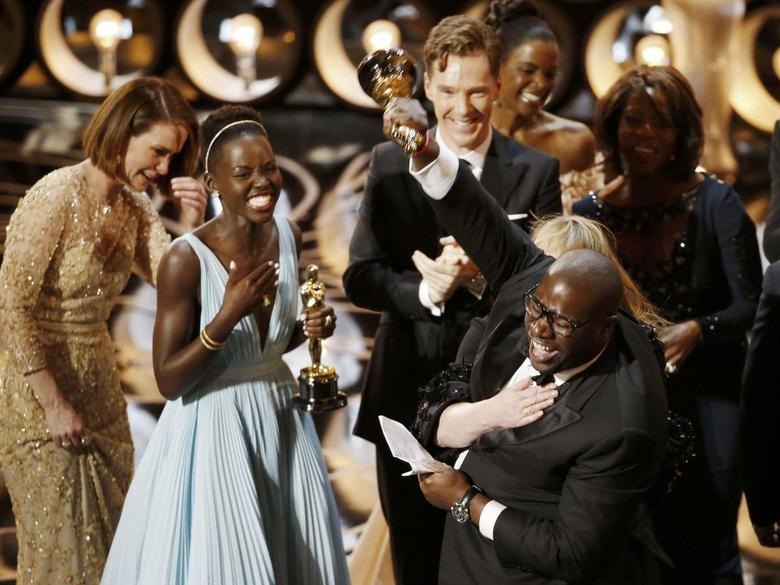 Director and producer Steve McQueen (R) celebrates after accepting the Oscar for best picture for his film ''12 Years a Slave'', with actress Lupita Nyong'o (L), at the 86th Academy Awards in Hollywood, California March 2, 2014. REUTERS/Lucy Nicholson