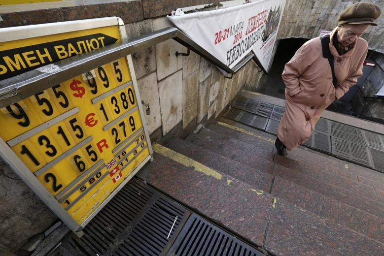 A woman passes a board with currency exchange rates in Kiev, February 26, 2014. REUTERS/Konstantin Chernichkin