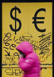 Женщина проходит мимо пункта обмена валют в Москве 3 марта 2014 года. Центральный банк РФ продал в понедельник до $10 миллиардов для поддержки рубя, считают дилеры. REUTERS/Maxim Shemetov