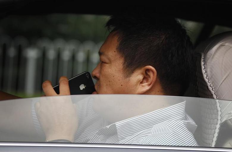 A man uses his iPhone as he drives a car along a main road in central Beijing September 24, 2012. REUTERS/David Gray