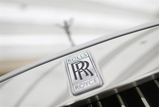 A Rolls-Royce mascot known as 'Spirit of Ecstasy' stands above the brand's logo on the front of a Rolls-Royce Ghost in a showroom in Singapore October 8, 2013. REUTERS/Tim Wimborne/Files