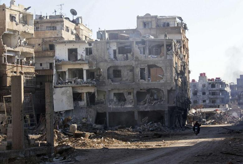 Men ride a motorcycle past buildings damaged by what activists said was shelling by forces loyal to Syria's President Bashar al-Assad in Daraya, near Damascus in this January 15, 2014 file photo. REUTERS/Hussam Zeen/Files