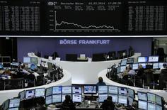 Operadores em suas mesas na frente do painel do índice DAX na bolsa de Frankfurt. Investidores europeus se assustaram nesta segunda-feira com a intervenção militar da Rússia na vizinha Ucrânia, o que arrastou o índice da zona do euro Euro STOXX 50 para sua maior queda diária desde junho. 03/03/2014 REUTERS/Remote/Stringer