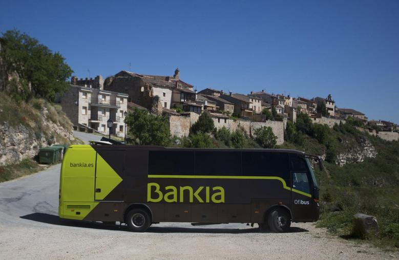 A travelling bank bus drives down the road after making its monthly call on customers in the village of Maderuelo, central Spain, June 4, 2013. REUTERS/Sergio Perez