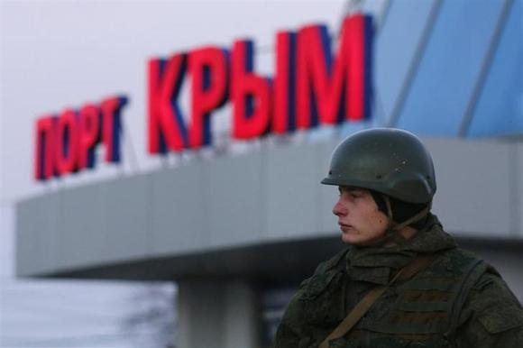 An armed man, believed to be a Russian soldier, stands outside the civilian port in the Crimean town of Kerch March 3, 2014. REUTERS/Thomas Peter