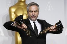 "Alfonso Cuaron poses with the awards for best director and best film editing for ""Gravity"" at the 86th Academy Awards in Hollywood, California March 2, 2014. REUTERS/Mario Anzuoni"