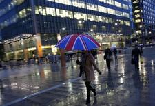 Workers walk in the rain at the Canary Wharf business district in London November 11, 2013. REUTERS/Eddie Keogh