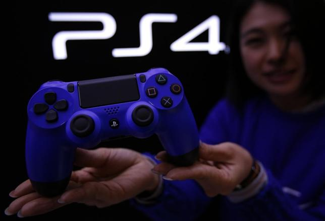 A staff at the PlayStation 4 launch event poses with PlayStation 4's game controller before its domestic launch event at the Sony Showroom in Tokyo February 21, 2014. REUTERS/Yuya Shino