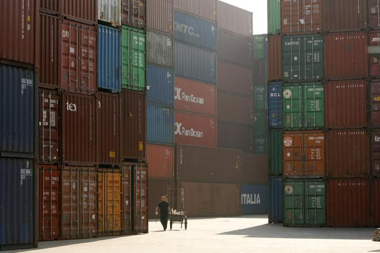 A woman walks past containers at a port in Shanghai January 13, 2009. REUTERS/Aly Song