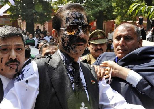 The Sahara group chairman Subrata Roy (C) with his face smeared in ink thrown by an unidentified man upon his arrival at the Supreme Court in New Delhi March 4, 2014. REUTERS/Stringer