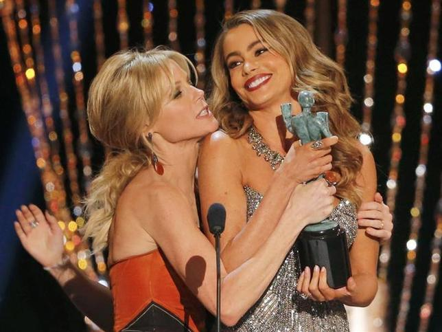Actresses Julie Bowen (L) and Sofia Vergara fight over the award for Outstanding Performance by an Ensemble in a Comedy Series for ''Modern Family'' as they joke around at the 20th annual Screen Actors Guild Awards in Los Angeles, California January 18, 2014. REUTERS/Mike Blake