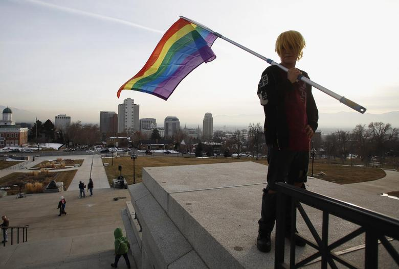 Corbin Aoyagi poses with a rainbow flag, as she joins supporters of same-sex marriage rally at Utah's State Capitol building in Salt Lake City, Utah January 28, 2014. REUTERS/Jim Urquhart