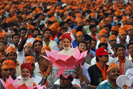 A supporter of Gujarat's chief minister and Hindu nationalist Narendra Modi, the prime ministerial candidate for India's main opposition Bharatiya Janata Party (BJP), wears a headgear with a portrait of Modi during a rally being addressed by Modi ahead of the 2014 general elections, in the western Indian city of Ahmedabad February 20, 2014. REUTERS/Amit Dave