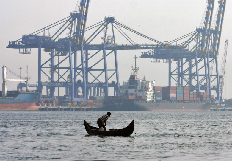 A fisherman prepares to cast his fishing net in the waters of the Vembanad lake as a container ship is seen docked in the background, at a port in Vallarpadam, in the southern Indian city of Kochi February 11, 2014. REUTERS/Sivaram V