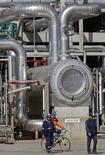 Trabalhadores andam pelas instalações da nova refinaria da petroleira portugesa Galp Energia, em Sines, depois de sua inauguração. A Galp aumentou levemente, na terça-feira, sua estimativa de investimentos para os próximos três a quatro anos para dar conta dos planos de crescimento da produção no Brasil e na África. 05/04/2013 REUTERS/Jose Manuel Ribeiro