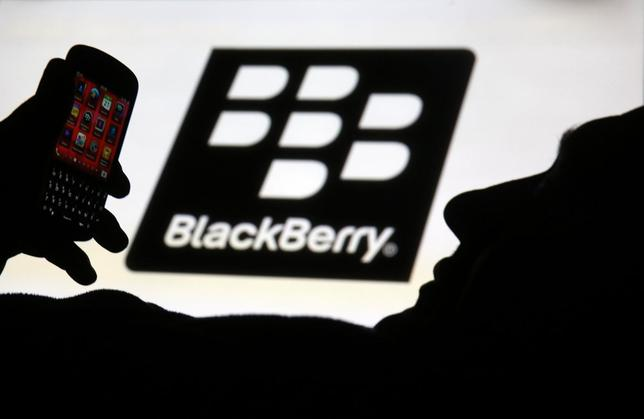 A man is silhouetted against a video screen with the Blackberry logo as he pose with a Blackberry Q10 in this photo illustration taken in the central Bosnian town of Zenica, September 21, 2013. REUTERS/Dado Ruvic