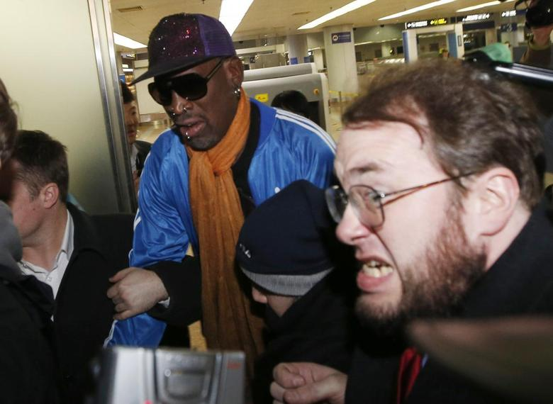 Bodyguards clear a path for former NBA basketball player Dennis Rodman (C) as journalists surround him upon his arrival from North Korea's Pyongyang at Beijing Capital International Airport January 13, 2014. REUTERS/Kim Kyung-Hoon