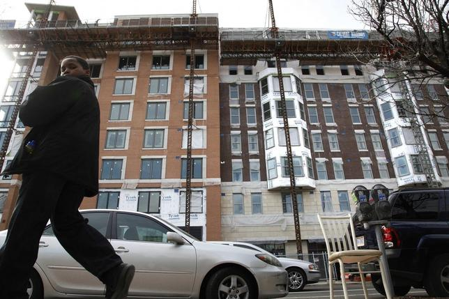 A youth walks past a construction site in the quickly developing Seventh Street corridor in Washington March 1, 2014. REUTERS/Jonathan Ernst