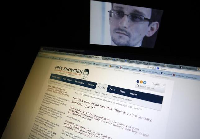 A portrait of former U.S. spy agency contractor Edward Snowden is displayed behind a screen as he answers users' questions on Twitter in this photo illustration in Sarajevo, January 23, 2014. REUTERS/Dado Ruvic