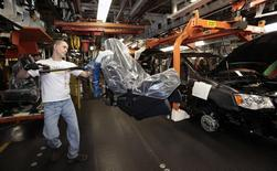 A Chrysler auto worker uses an ergo-arm to load the seats into Chrysler minivans during the production launch of the new 2011 Dodge Grand Caravan's and Chrysler Town & Country minivans at the Windsor Assembly Plant in Windsor, Ontario January 18, 2011. REUTERS/Rebecca Cook