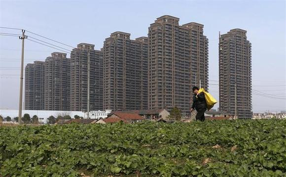 A farmer walks past a vegetable field near newly-built residential buildings in Jiaxing, Zhejiang province February 23, 2014. REUTERS/William Hong/Files
