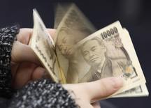 Женщина пересчитывает купюры валюты иена в Токио 28 февраля 2013 года. Курс иены стабилизировался к доллару после резкого падения во вторник, вызванного обещанием президента РФ Владимира Путина без крайней необходимости не применять военную силу на Украине. REUTERS/Shohei Miyano
