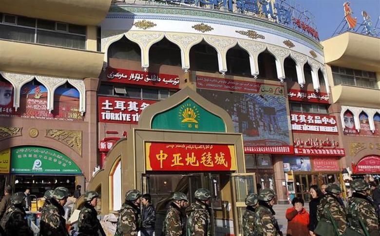 Paramilitary policemen walk past Erdaoqiao Grand Bazaar in Urumqi, Xinjiang Uighur autonomous region, November 17, 2013. REUTERS/Rooney Chen