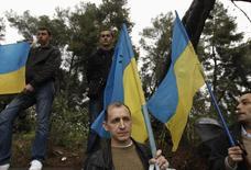 Manifestantes pró-Ucrânia com bandeiras do país durante um protesto fora da embaixada russa em Atenas. A União Europeia está pronta para fornecer 11 bilhões de euros em ajuda financeira à Ucrânia nos próximos dois anos através de uma série de empréstimos e concessões, afirmou nesta quarta-feira o presidente da Comissão Europeia, José Manuel Barroso. 03/04/2014 REUTERS/Alkis Konstantinidis