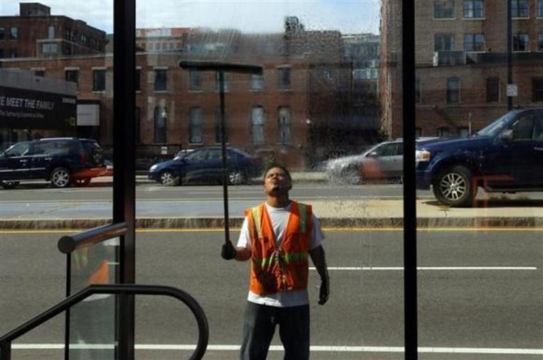 A worker washes the windows of a silver line bus station in Boston, Massachusetts August 12, 2013. REUTERS/Brian Snyder