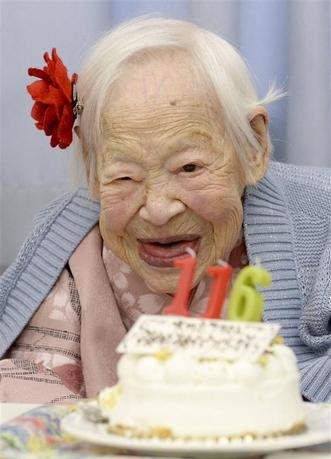 Japanese Misao Okawa, the world's oldest woman, poses for a photo next to her birthday cake as she celebrates her 116th birthday in Osaka, western Japan, in this photo taken by Kyodo March 5, 2014. Okawa celebrated her 116th birthday on Wednesday. Mandatory credit. REUTERS/Kyodo