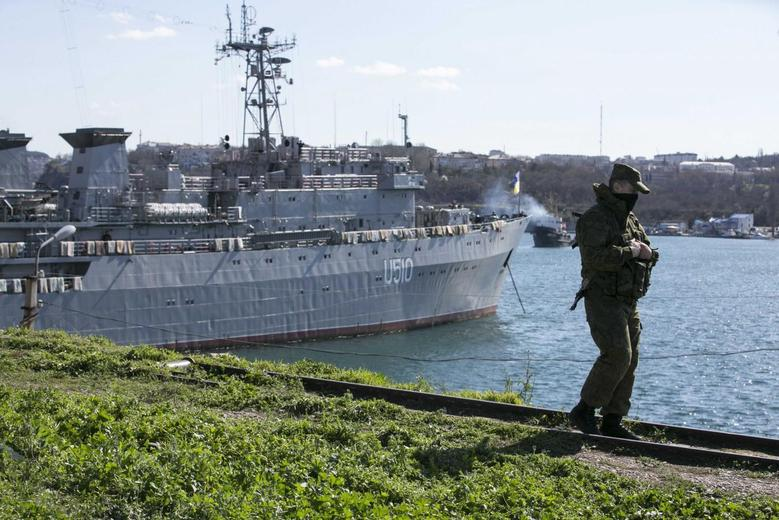 A Russian soldier stands guard near Ukrainian navy command ship Slavutych at the Crimean port of Sevastopol March 5, 2014. REUTERS/Baz Ratner