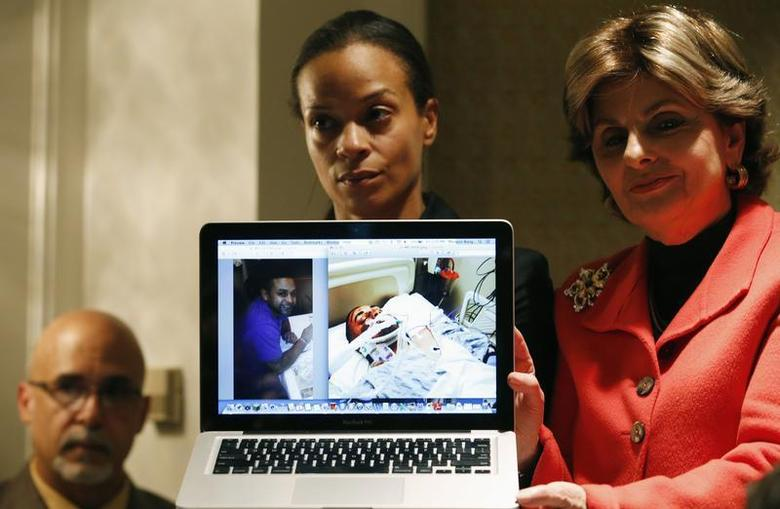 Attorney Gloria Allred (R) helps Dayana Mejia hold up a laptop showing a photograph of her hospitalized partner Edwin Mieses, during a news conference in New York, October 4, 2013. REUTERS/Mike Segar