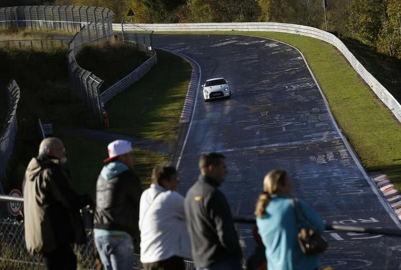 Motorsport enthusiasts watch hobbyist racers steer their super-charged cars into the Breidscheid section of the legendary 13-mile (21-km) Nuerburgring race track, in the western German low mountain range of the Eifel near Adenau, October 27, 2013. REUTERS/Wolfgang Rattay
