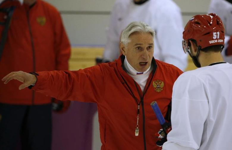 Russia's men's ice hockey coach Zinetula Bilyaletdinov (C) talks to players during a team practice at the 2014 Sochi Winter Olympics, February 14, 2014. REUTERS/Grigory Dukor