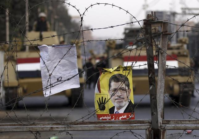 A poster of ousted Egyptian President Mohamed Mursi is pictured on barbed wires during a protest by his supporters at El-Thadiya presidential palace in Cairo November 15, 2013. REUTERS/Amr Abdallah Dalsh