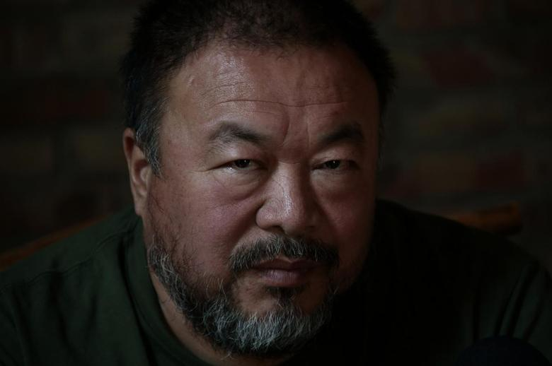 Dissedent Chinese artist Ai Weiwei looks up during a group interview at his studio in Beijing, May 22, 2013. REUTERS/Petar Kujundzic