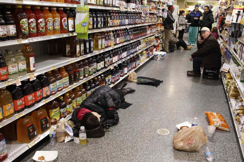 People rest at the aisle of a Publix grocery store after being stranded due to a snow storm in Atlanta, Georgia, January 29, 2014. REUTERS/Tami Chappell