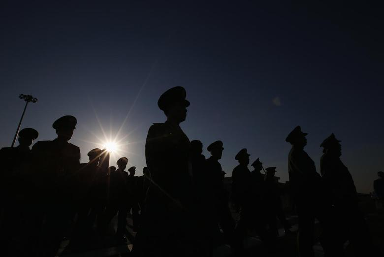 Military delegates are silhouetted as they arrive at Tiananmen Square outside the Great Hall of the People for the opening session of National People's Congress (NPC), in Beijing, March 5, 2014. REUTERS/Kim Kyung-Hoon
