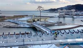 """The replica of a lone pine tree that survived the 2011 earthquake and tsunami disaster, now labelled the """"miracle pine"""" as it became a symbol of hope for the region, is seen behind a huge belt conveyor which carries soil and sand from mountains to raise the ground above sea level in Rikuzentakata, Iwate prefecture, in this February 13, 2014 picture provided by Kyodo. Mandatory credit REUTERS/Kyodo"""