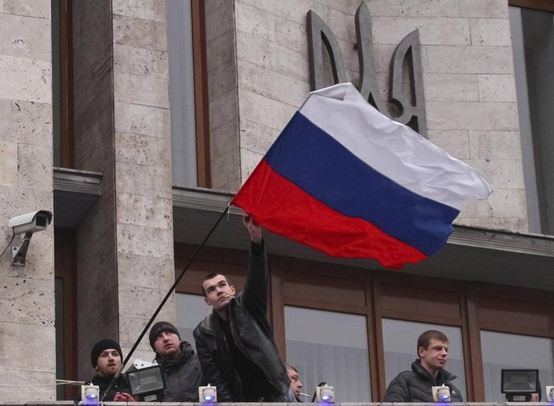 Pro-Russian demonstrators erect a Russian flag outside the regional government building in Donetsk March 5, 2014. REUTERS/Stringer
