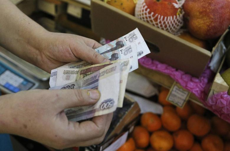 A vendor counts Russian ruble banknotes at a market in Moscow, March 3, 2014. REUTERS/Maxim Shemetov