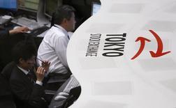 Сотрудники Tokyo Stock Exchange (TSE) перед началом торгов в Токио 30 декабря 2013 года. Азиатские фондовые рынки выросли в четверг на фоне дипломатических усилий по разрешению политического кризиса на Украине и локальных новостей. REUTERS/Yuya Shino