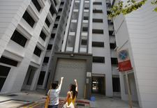 A resident (L) shows where she said the body of Autumn Radkte, chief executive of First Meta Pte Ltd, was found on the second floor of a public housing estate, in Singapore March 6, 2014. REUTERS/Edgar Su