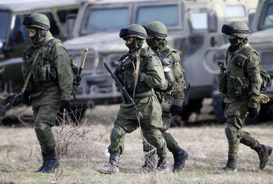 Uniformed men, believed to be Russian servicemen, walk near a Ukrainian military base in the village of Perevalnoye, outside Simferopol, March 6, 2014. REUTERS-Vasily Fedosenko