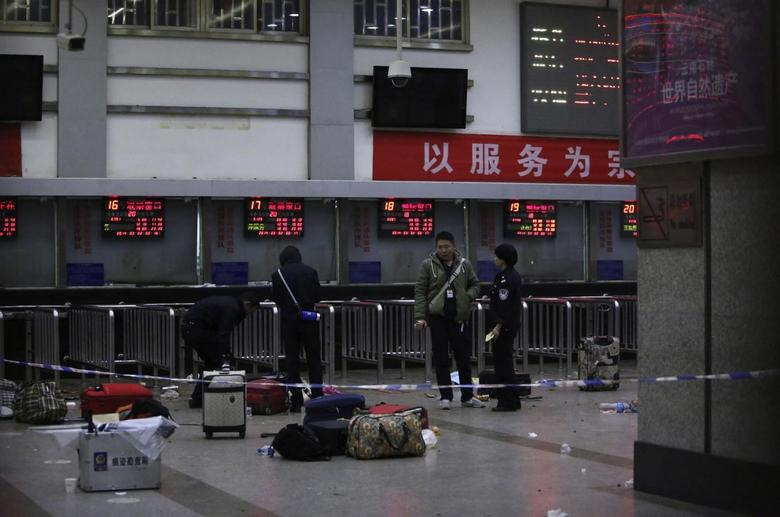 Police stand near luggages left at the ticket office after a group of armed men attacked people at Kunming railway station, Yunnan province, March 2, 2014. REUTERS/Stringer