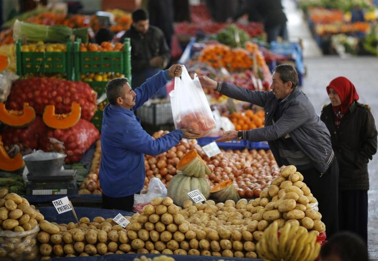 A vendor sells potatoes and other vegetables to a customer in an open market in central Ankara February 5, 2014. REUTERS/Umit Bektas