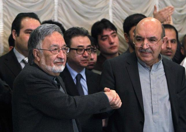 Afghan presidential candidate Qayum Karzai (R) shakes hand with fellow presidential candidate Zalmai Rassoul during a news conference in Kabul March 6, 2014. REUTERS/Omar Sobhani