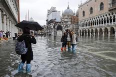 Tourists pose for a photo in a flooded St. Mark's Square during a period of seasonal high water in Venice January 31, 2014. REUTERS/Manuel Silvestri