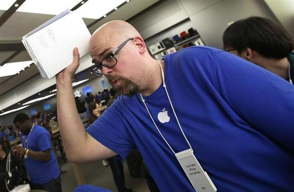 An employee carries new Apple iPad Air tablets for customers inside the Apple Store on New York's fifth avenue, after the new iPad went on sale, November 1, 2013. REUTERS/Mike Segar/Files